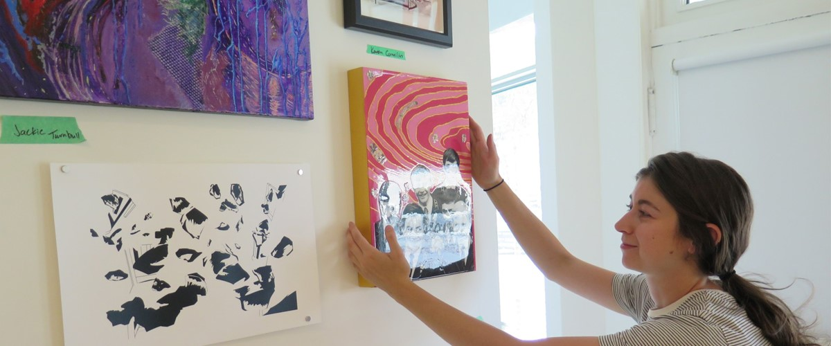A woman putting her oil painting on the wall after the sucessfull Fine Art Removals in Australia
